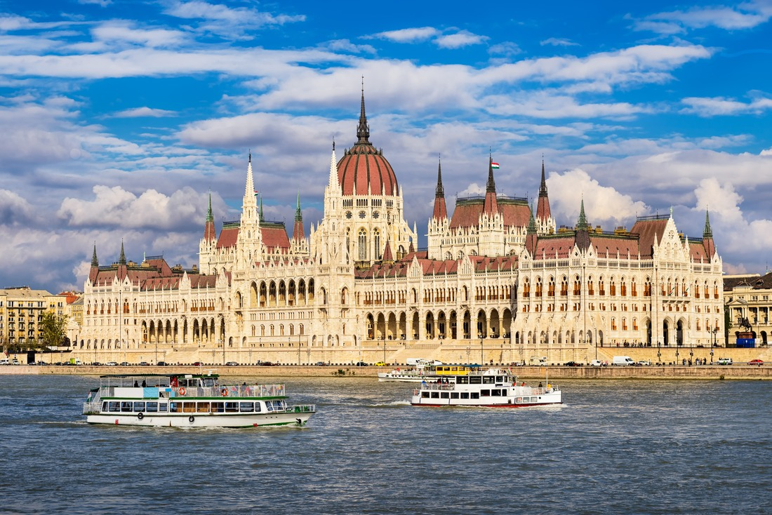 Small ships cruising next to Parliament building in Budapest, Hungary
